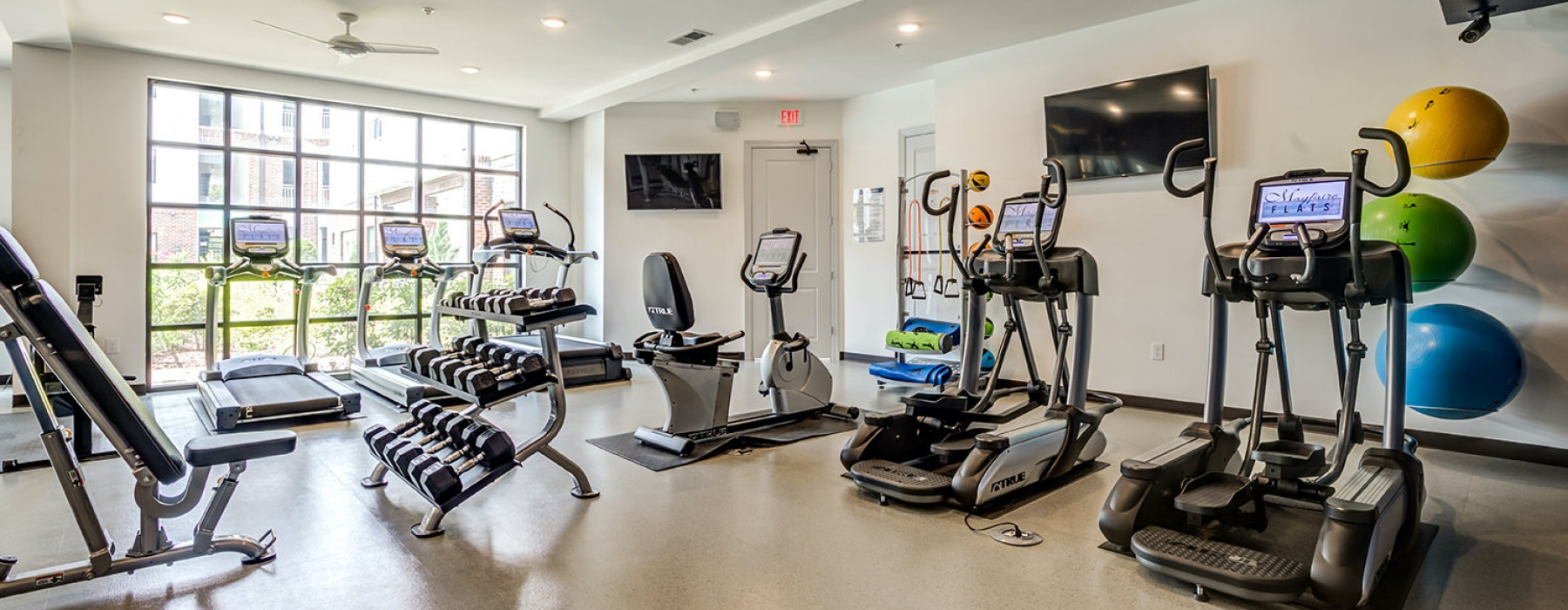 Open fitness center with warm, recessed lighting and a variety of equipment