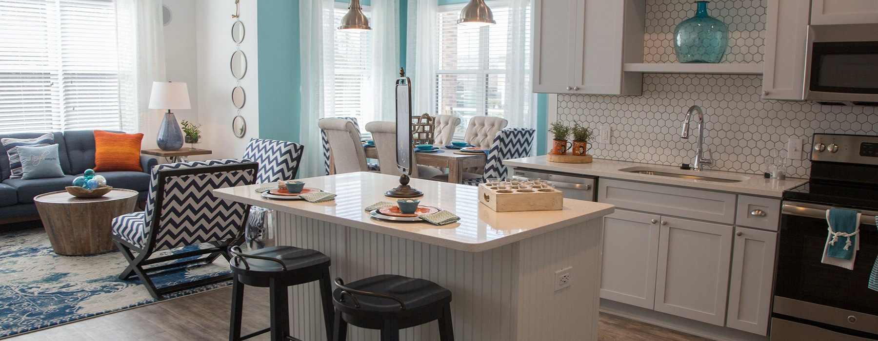 Costal kitchen, living, and dining space with large windows for lighting