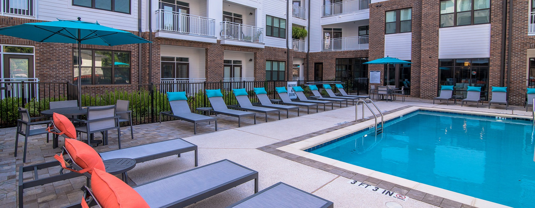 Pool enclosed by apartment units with lots of outdoor seating